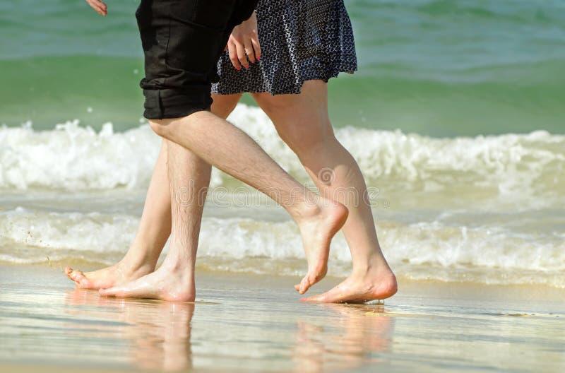 Romantische junge Paare am Feiertag, der entlang Strand geht stockfotos
