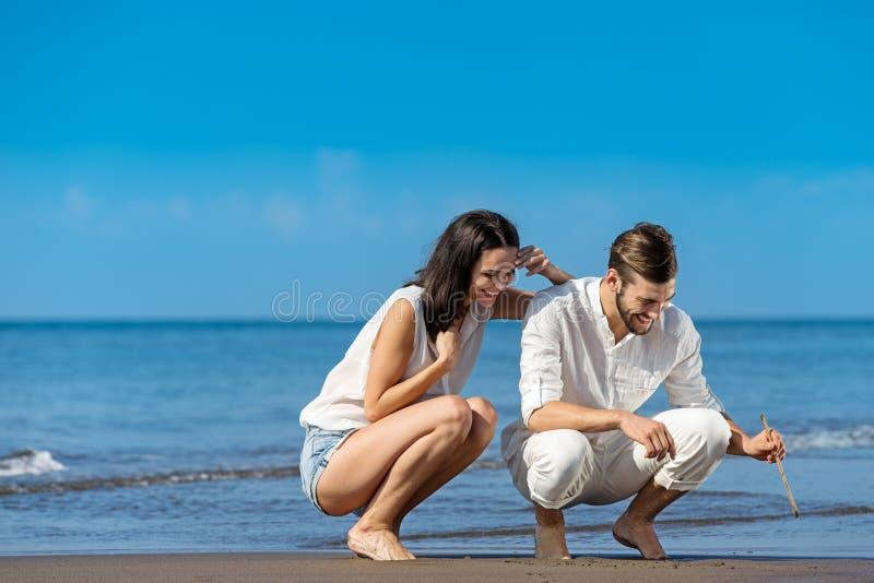 Romantische junge Paare zeichnen Formen im Sand während auf Flitterwochen lizenzfreies stockbild