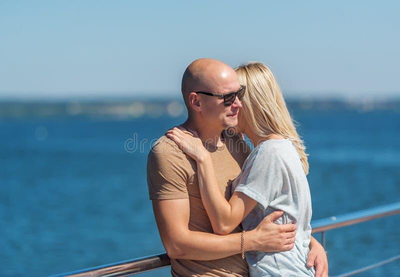 Romantische junge schöne Paare, die auf Pier von Fluss stehen lizenzfreies stockbild