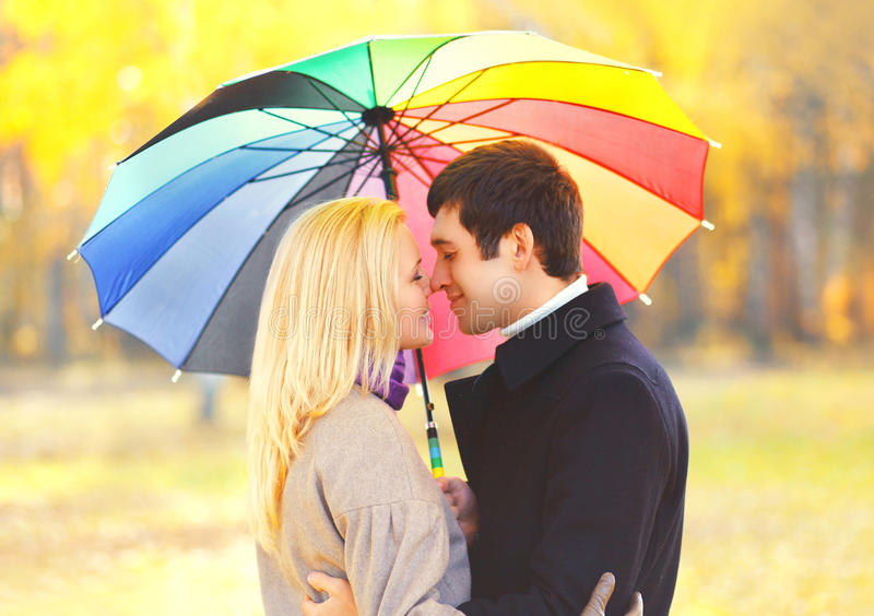 Romantische küssende Paare des Porträts in der Liebe mit buntem Regenschirm zusammen am warmen sonnigen Tag über gelben Blättern lizenzfreie stockfotos
