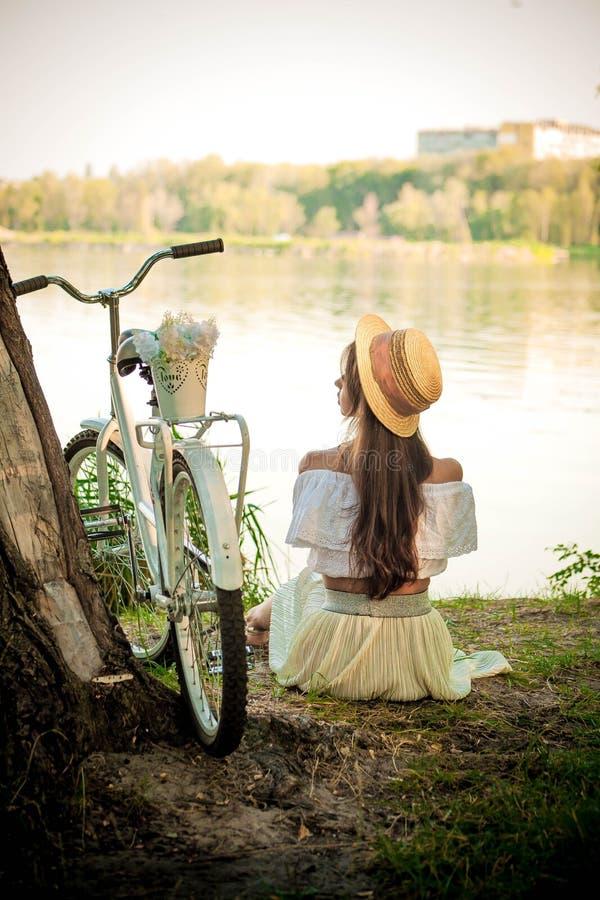 Romantische meisjeszitting onder een boom door het meer royalty-vrije stock foto