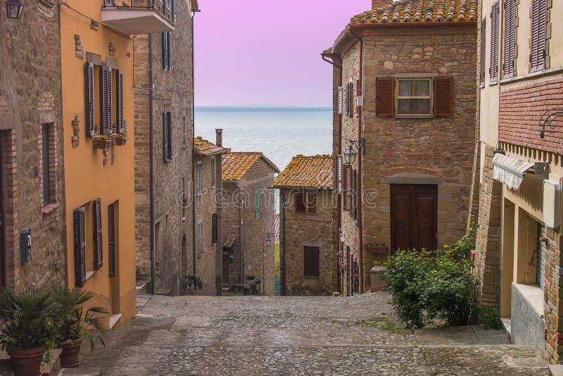 Romantische mening van het middeleeuwse dorp van Monte del Lago op Trasimeno-meer bij zonsondergang royalty-vrije stock foto's