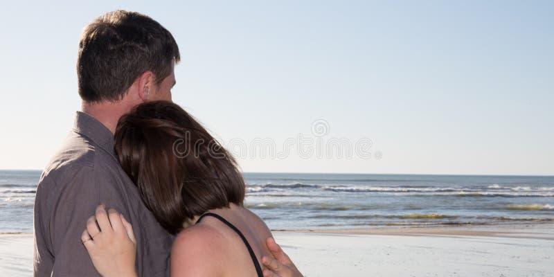 Romantische Mitte gealterte Paare, die schönen Sonnenuntergang auf dem Strand genießen stockfotografie