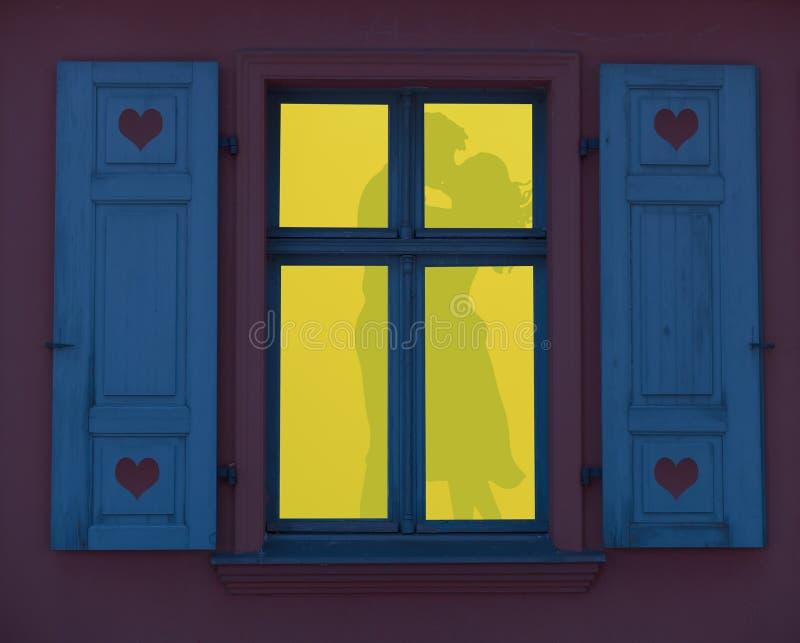 Romantische nacht, een silhouet van een paar die liefde in een aangestoken venster maken royalty-vrije stock afbeeldingen