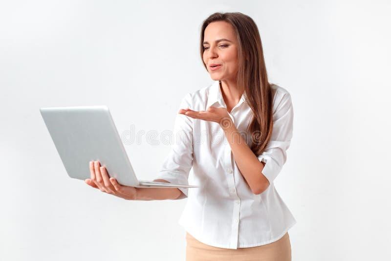 Romantische online mededeling Vrouw status geïsoleerd op wit die videopraatje op laptop hebben die luchtkus verzenden naar camera stock afbeeldingen