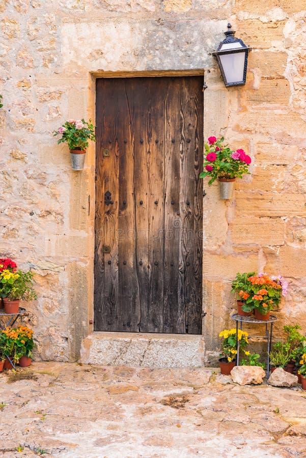 Romantische oude houten voordeur met bloemendecoratie stock foto