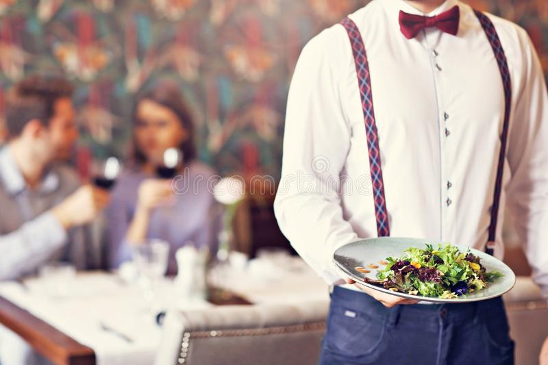 Romantische Paardatierung im Restaurant, das vom Kellner gedient wird lizenzfreie stockfotos