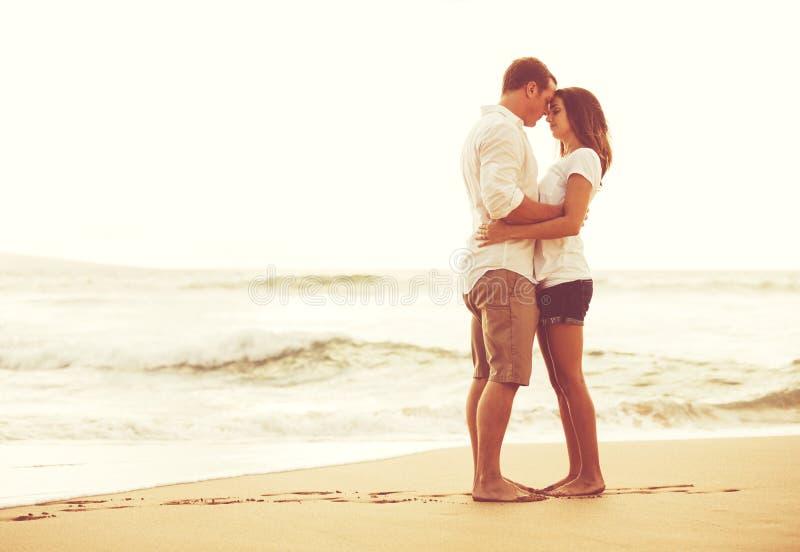 Romantische Paare auf dem Strand bei Sonnenuntergang lizenzfreie stockbilder