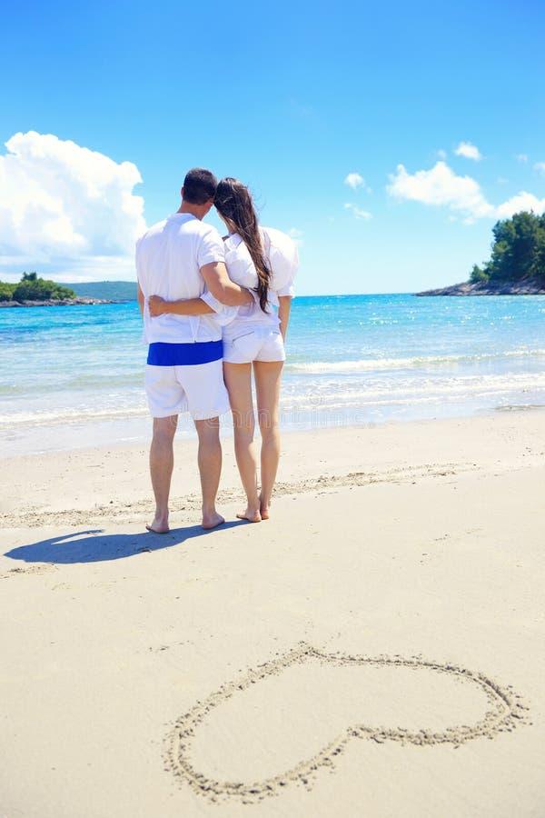 Romantische Paare in der Liebe haben Spaß auf dem Strand mit Herz drawi lizenzfreie stockbilder
