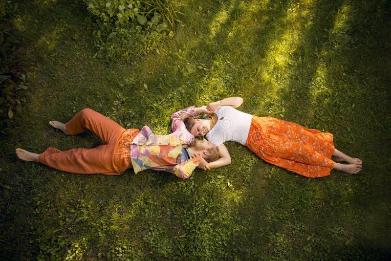 Romantische Paare der Schönheit, die draußen liegen umfassen stockbild