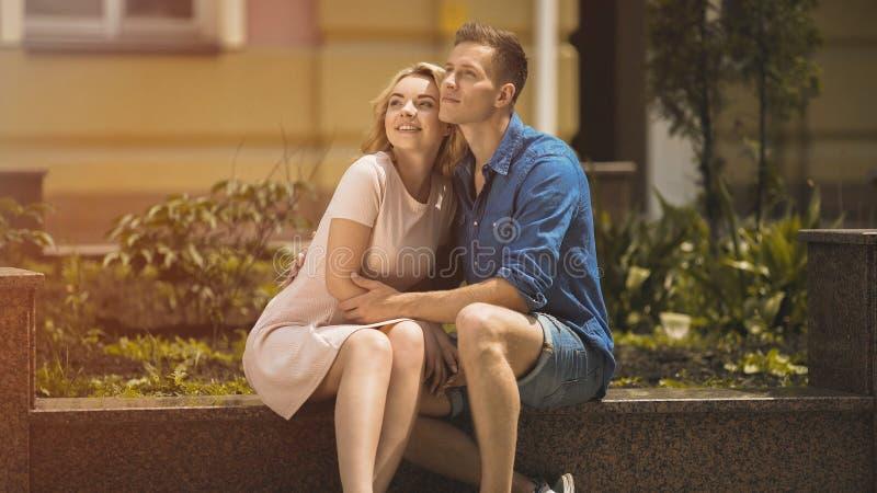Romantische Paare, die auf Bank sitzen und glückliche Zukunft, zarte Gefühle untersuchen stockbilder