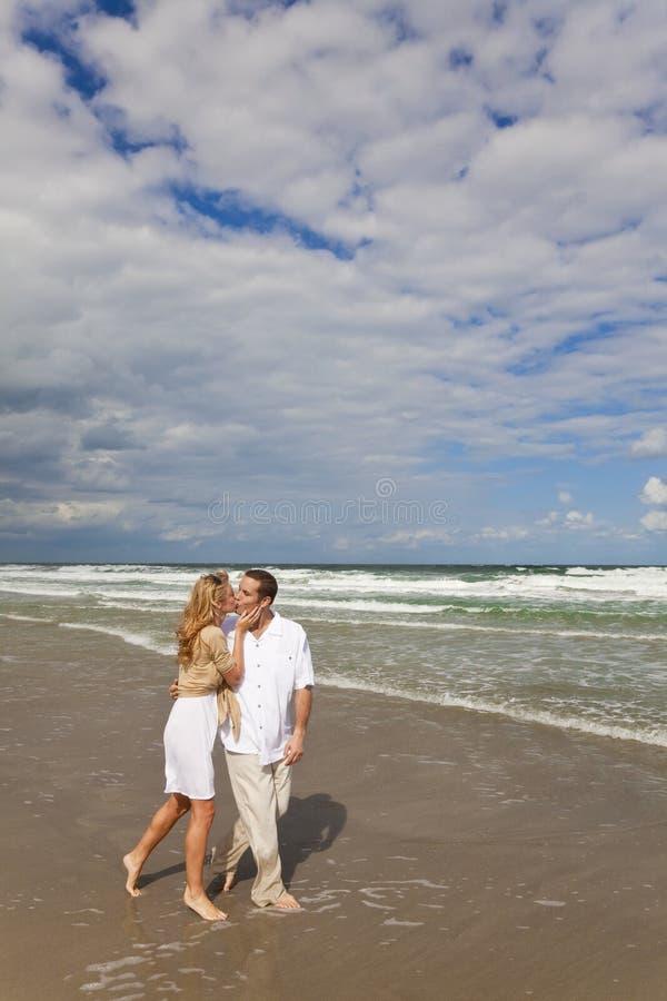 Romantische Paare, die auf einem Strand gehen und küssen stockbilder