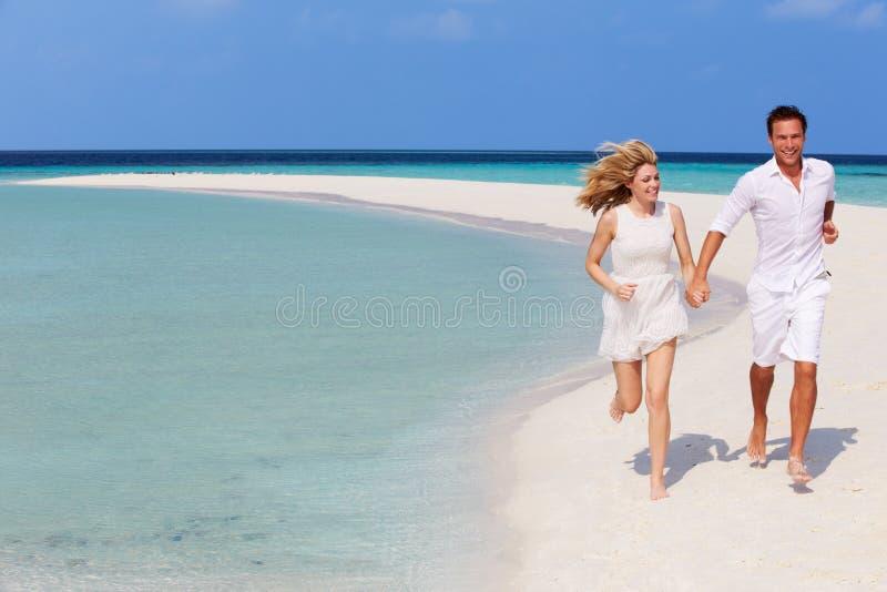 Romantische Paare, die auf schönem tropischem Strand laufen lizenzfreies stockbild