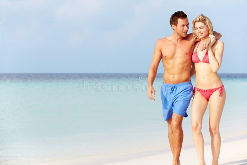 Romantische Paare, die auf schönen tropischen Strand gehen stockbild