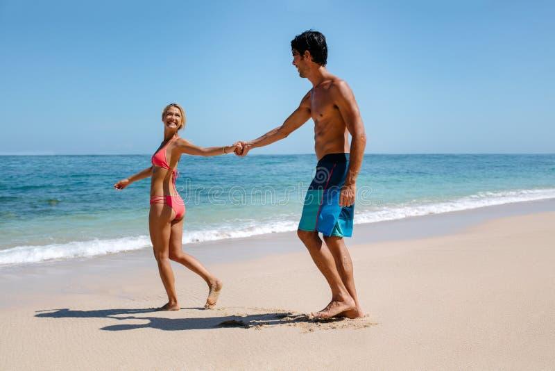 Romantische Paare, die auf schönen tropischen Strand gehen stockfoto