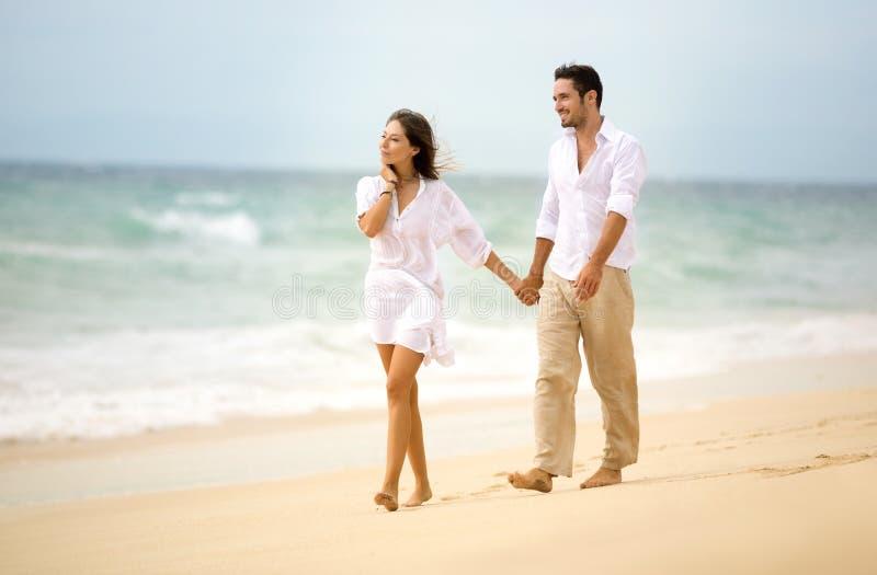 Romantische Paare, die auf Strand gehen stockfoto