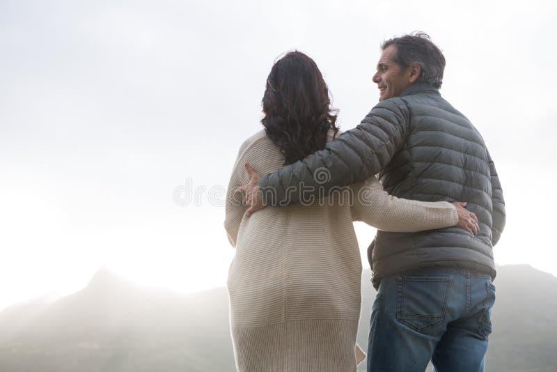 Romantische Paare, die auf Strand sich umfassen stockfoto