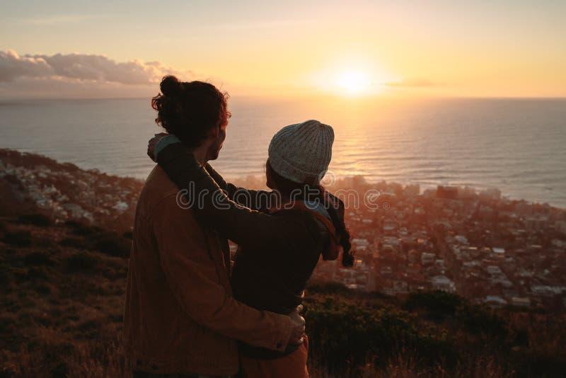 Romantische Paare, die den Sonnenuntergang von der Spitze bewundern lizenzfreies stockfoto