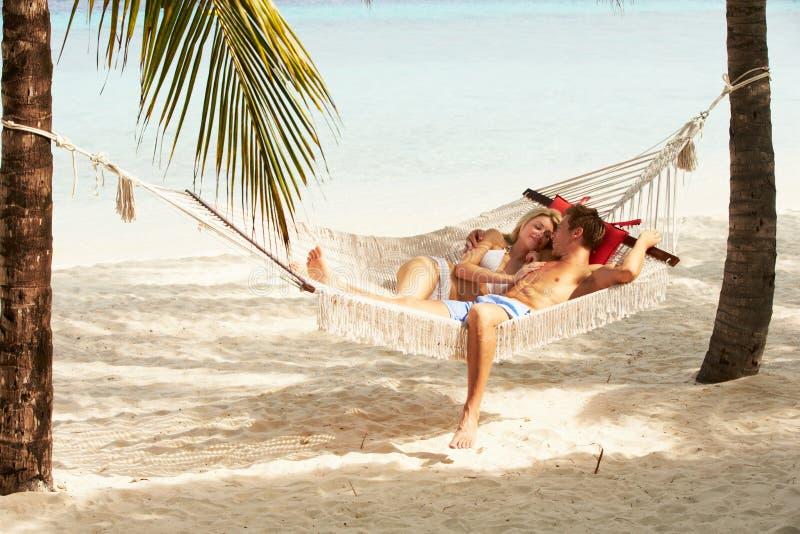 Romantische Paare, die in der Strand-Hängematte sich entspannen stockbilder