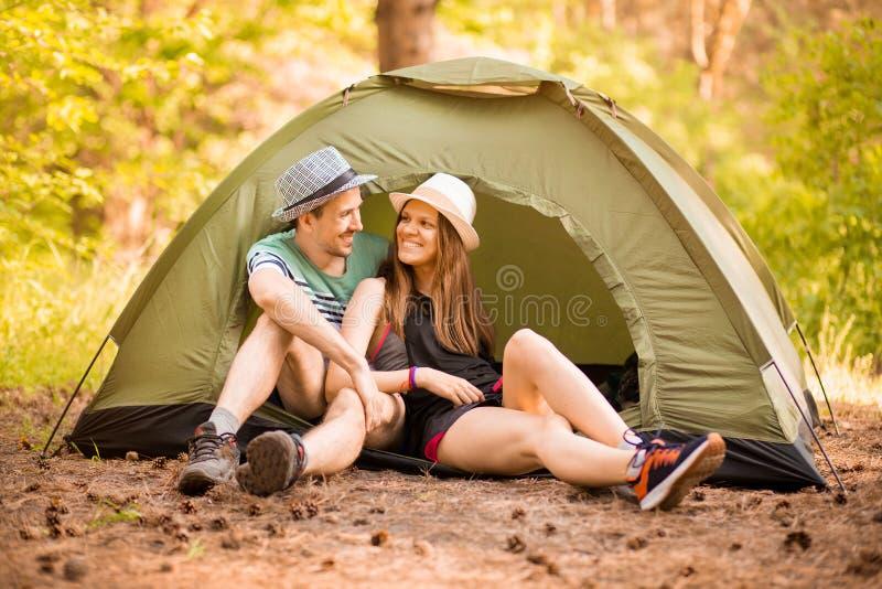Romantische Paare, die drau?en kampieren und im Zelt sitzen Glücklicher Mann und Frau auf romantischen Ferien stockfoto