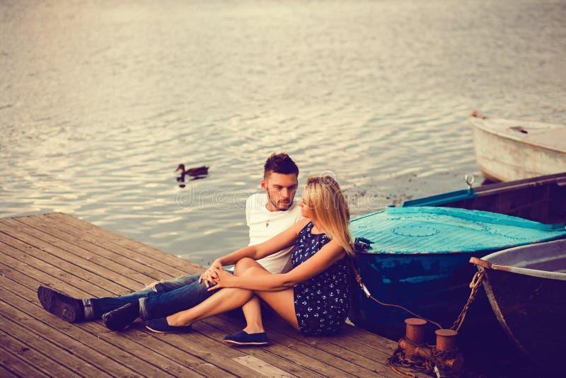 Romantische Paare, die durch den See sitzen stockbilder