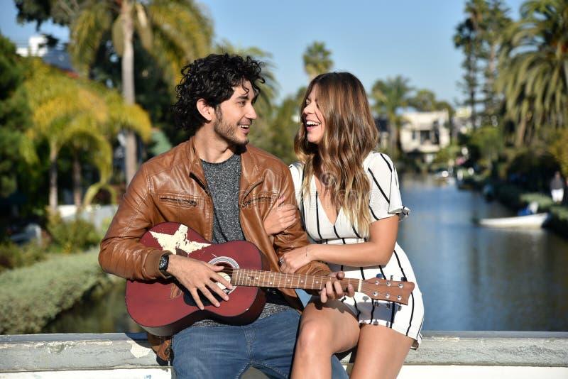 Romantische Paare, die Gitarre über ruhigem Kanal spielen lizenzfreie stockfotografie