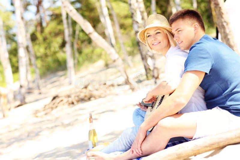 Romantische Paare, die Gitarre am Strand spielen stockfotos