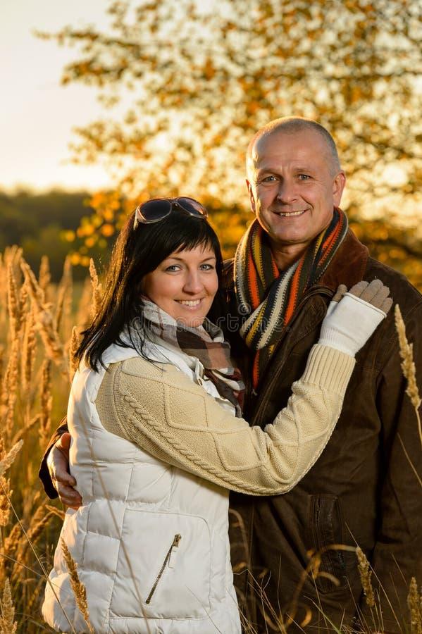 Romantische Paare, die Herbstsonnenunterganglandschaft umarmen stockfotografie