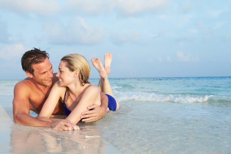 Romantische Paare, die im Meer auf tropischem Strandurlaub liegen lizenzfreies stockfoto