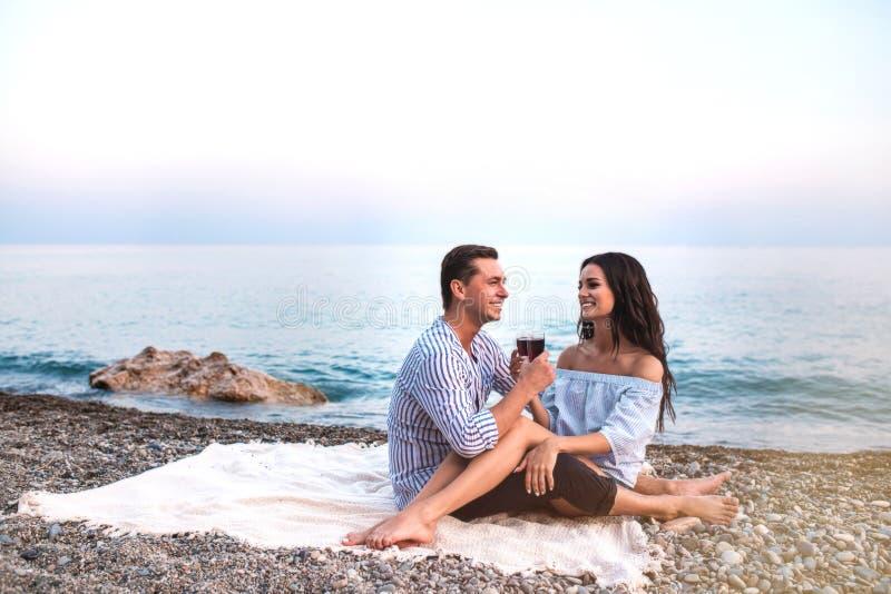 Romantische Paare, die mit Weingläsern an der Küste bei Sonnenuntergang sitzen stockfotografie