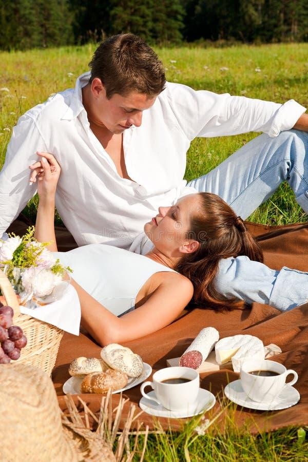 Romantische Paare, die Picknick in der Wiese haben stockfotos