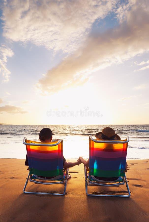 Romantische Paare, die schönen Sonnenuntergang genießen lizenzfreie stockfotografie