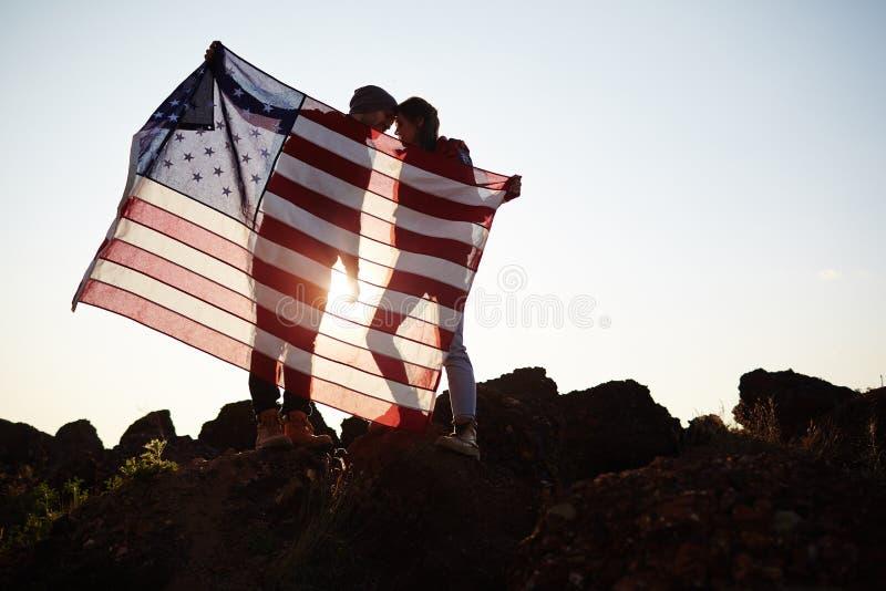 Romantische Paare, die USA-Flagge auf die Oberseite halten stockbild