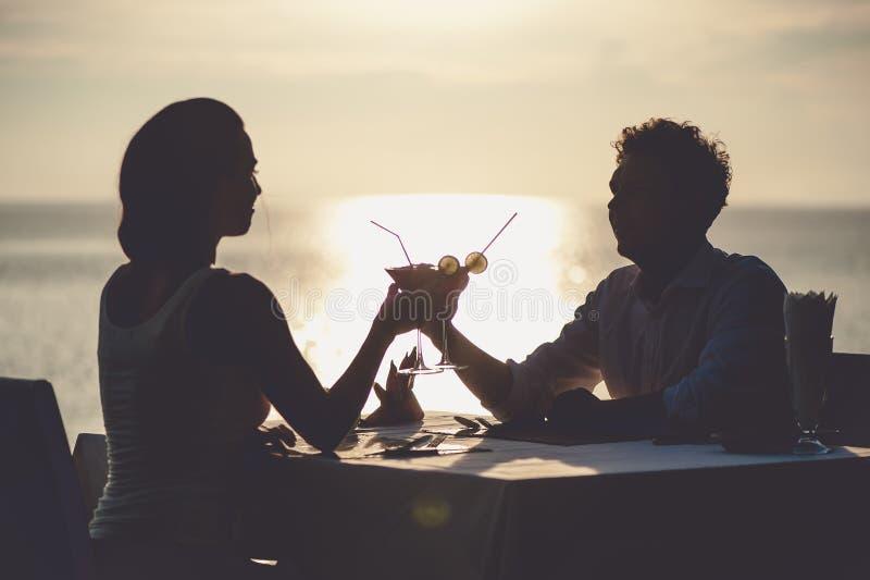 Romantische Paare genießen Sonnenuntergang im Restaurant auf den trinkenden Cocktails des Strandes stockfotografie