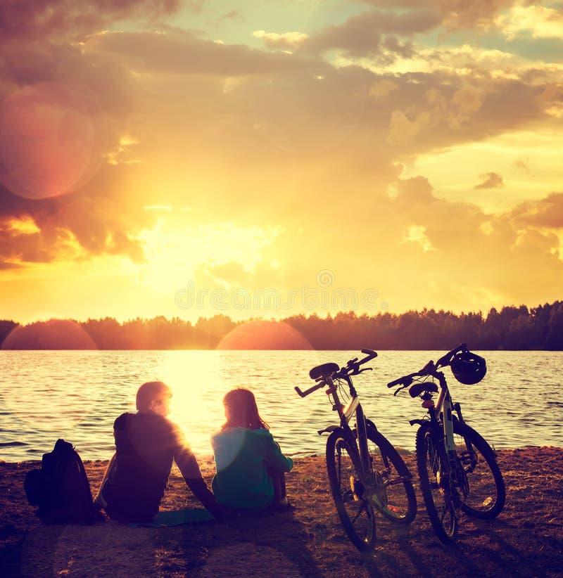 Romantische Paare mit Fahrrädern durch den See stockbilder