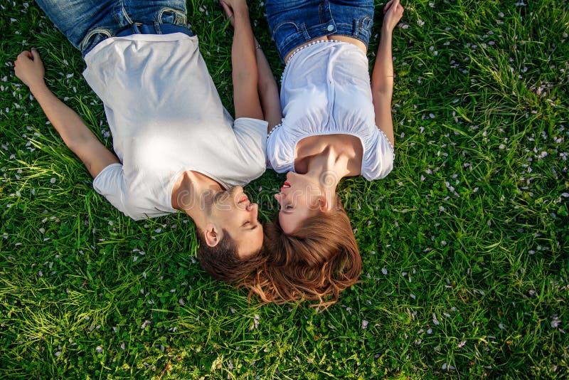Romantische Paare von den jungen Leuten, die auf Gras im Park liegen Sie legen auf die Schultern von einander und halten Hände zu stockfoto