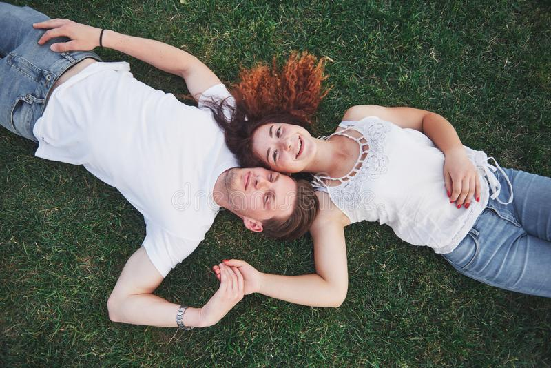 Romantische Paare von den jungen Leuten, die auf Gras im Park liegen Sie schauen glücklich Ansicht von oben stockfoto