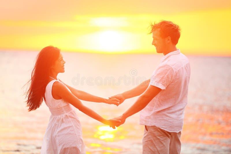 Romantische paarminnaars die handen, strandzonsondergang houden