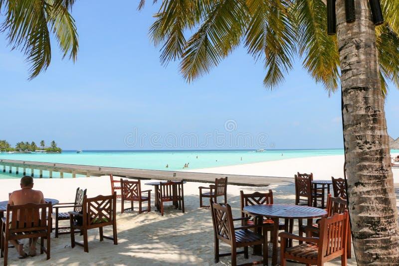 Romantische Restauranttabelle und -stühle im Freien am Strand auf Sonne lizenzfreies stockfoto