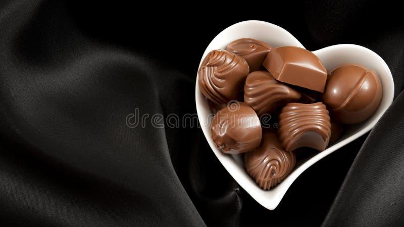 Romantische süße Geschenke für Valentinsgruß-Tageskonzept mit einem Herzen formten die Schüssel, die mit Schokoladenpralinen auf  lizenzfreie stockfotografie