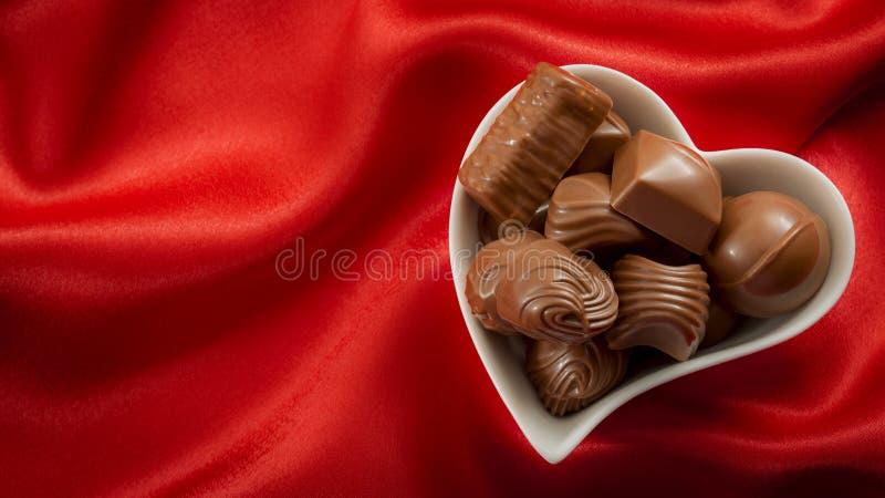 Romantische süße Geschenke für Valentinsgruß-Tageskonzept mit einem Herzen formten die Schüssel, die mit Schokoladenpralinen auf  lizenzfreies stockfoto