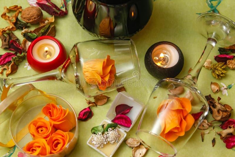 Romantische samenstelling met wijnglas, rozen, juwelen, kaarsen en fles wijn stock fotografie