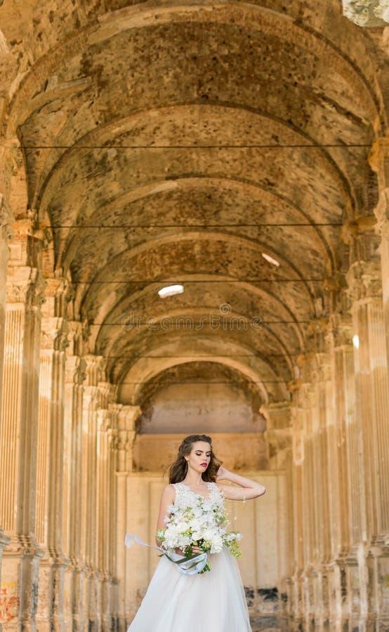Romantische schöne Braut in der Luxuskleideraufstellung der schönen Architektur stockfotografie