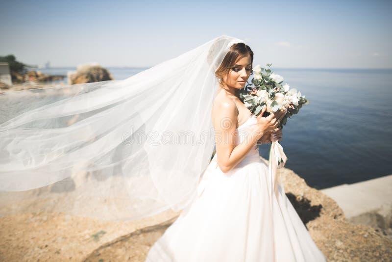 Romantische schöne Braut im weißen Kleid, das auf dem Hintergrundmeer aufwirft lizenzfreie stockfotografie