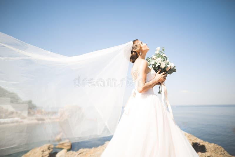 Romantische schöne Braut im weißen Kleid, das auf dem Hintergrundmeer aufwirft stockfotografie