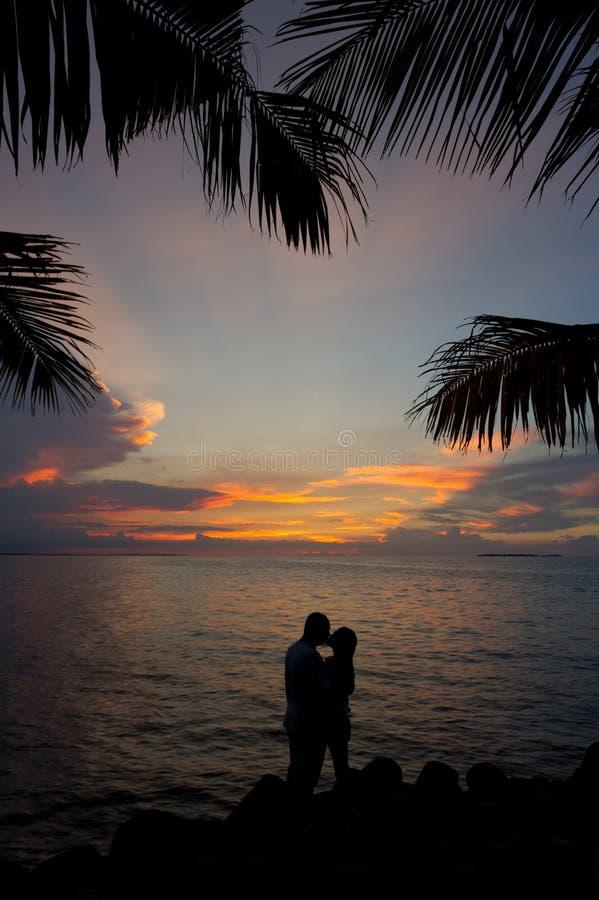 Romantische Schattenbildpaare, die im Sonnenuntergang küssen lizenzfreie stockfotos