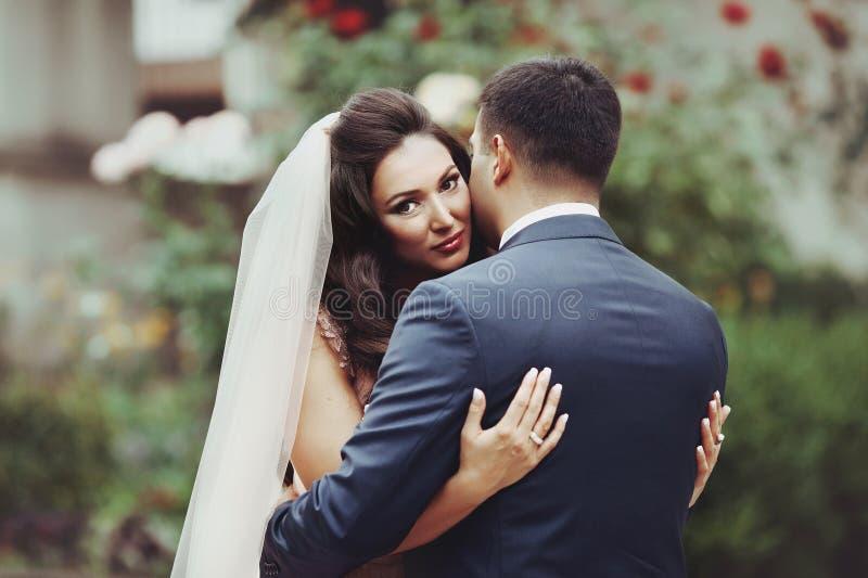Romantische, sinnliche Paare - Braut und Bräutigam, der draußen mit umarmt lizenzfreie stockfotografie