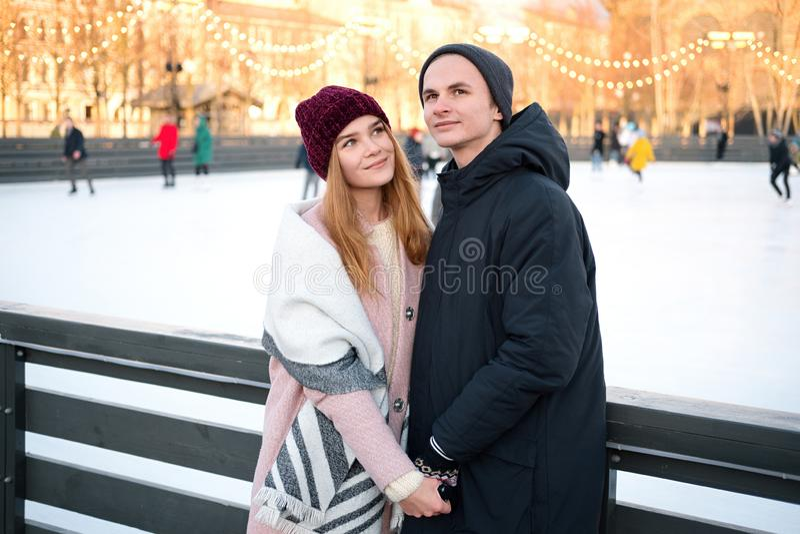 Romantische sorglose Paare im Liebeshändchenhalten, das zusammen romantischen Moment draußen nahe Eisbahn im Winter genießt stockfoto