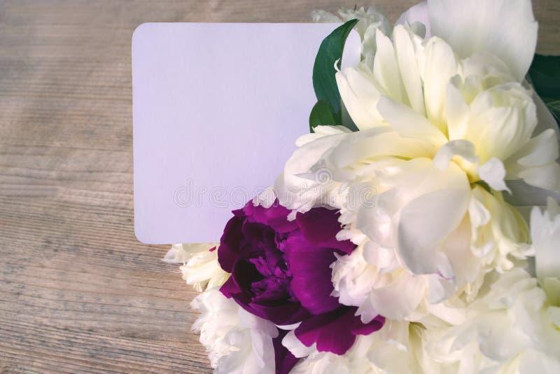 Romantische stemming - een boeket van pioenbloemen met een nota Foto in warme kleuren wordt gekleurd die stock foto's