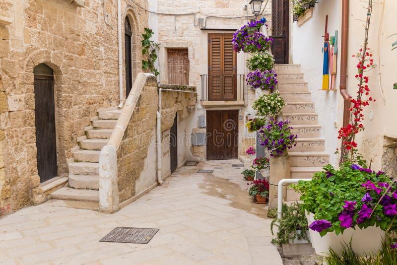 Romantische straten van Polignano een Merrie oude die stad met gedichten op treden, Apulia-gebied, Zuiden worden geschreven van I stock afbeeldingen